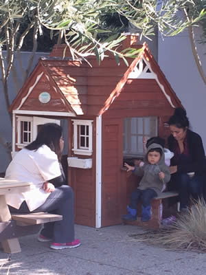 Child and teacher in front of play house.